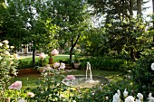 Pond with fountain surrounded by trees and roses ('Iceberg', 'Gloria Dei') in extensive gardens