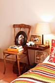 Mit Flohmarktartikeln und Bildern dekorierter Nachttisch neben gemütlichem Mustermix auf Bett im Schlafzimmer