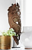 Antique, carved sculpture, plant in brass pot and ceramic vase on windowsill