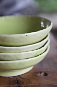 Stack of four green-glazed clay dishes