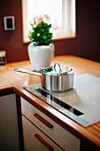 Stainless steel saucepan on hob built into corner worksurface of fitted kitchen