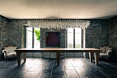 Chandelier made from 200 stemware glasses above long dining table in salon of Italian farmhouse