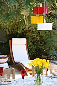 Pendant lamps upcycled from cake-tins painted various colours above terrace table, wooden lounger with white cushions in front of palm tree