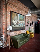 Large oil painting on brick wall of industrial-style loft apartment with retro sofa and armchair
