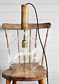 Retro pendant lamp with glass lampshade on nostalgic wooden chair against white wooden wall