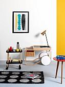 Copper lamp on serving trolley below modern artwork on wall