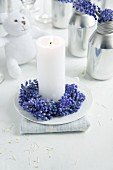 White candle with wreath of grape hyacinths