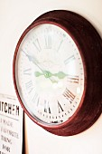 Round wall clock with antique-style Roman numerals