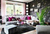 Comfortable corner sofa, grey patterned wallpaper, hot pink scatter cushions and family photos on wall