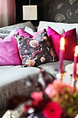 Grey sofa with pink scatter cushions and romantic lit candles in foreground