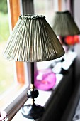 Antique table lamp with fabric lampshade on windowsill