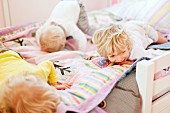 Three young brothers crawling face down on bed