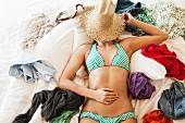 Woman in bikini sleeping on messy bed