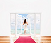 Woman opening French doors to ocean view