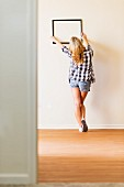Blonde woman holding black picture frame on wall