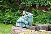 Gartendeko: Froschkönig aus Stein auf Brunnenrand