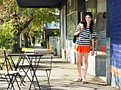 Young woman with takeaway coffee at pavement cafe