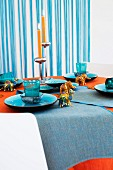 Table set with blue crockery, small elephant and other animal figurines and candlesticks