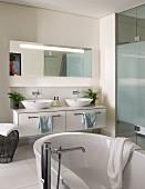 Elegant bathroom with bathtub, washstand with twin sinks and glazed shower area