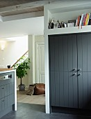 Fitted cupboard with wooden doors painted dark grey below shelf niche and view through open doorway into hall