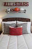 All-Stars-Schriftzug und Netz mit verschiedenen Bällen als Wanddeko über Bett mit Zierkissen