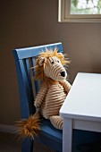Soft toy sitting on child's chair at table below window