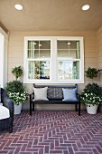 Covered porch with brick flooring and bench