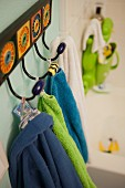 Close-up of towels hanging on hooks in bathroom