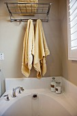 Bathroom with towels hanging over bathtub; San Marcos; California; USA