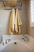 Aufgehängte Handtücher über weisser Badewanne