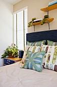 Bett mit blauem Kopfteil & Dekokissen, darüber zwei Wandregale aus Holz