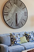 Cropped couch with large wall clock in living room; San Marcos; California; USA