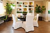Wohnraum mit rundem Esstisch, Hussenstühlen & von Grünpflanzen eingerahmtem Regalschrank