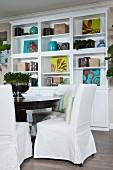 weiße Hussenstühle an rundem Esstisch vor weißem Regalschrank mit Büchern & Dekoobjekten