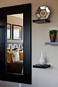 Bett spiegelt sich in rechteckigem Wandspiegel, daneben Wandkonsolen mit Dekoobjekten