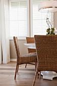 Korbstühle an rundem Esstisch mit weisser Deckenleuchte