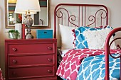 Bedside table and wrought iron bed in bedroom