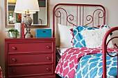 Schlafzimmer mit rotem Metallbett & roter Kommode als Nachttisch