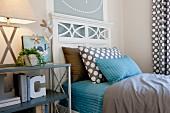 Holzbett mit weißem Kopfteil, Bettwäsche & Kissen in Blau und Braun sowie Regal als Nachttisch