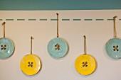 Blaue und gelbe Knöpfe als Wanddeko in Kinderzimmer
