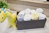 Aufgerollte Handtücher in stoffbezogener Box daneben Stofftier