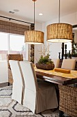 Chairs at dining table below round pendant lamps; Moreno Valley; California;