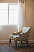 Upholstered armchair below window