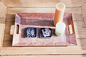 Candles on tray on wooden table in sunlight; Dana Point; California; USA