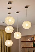 Close-up of lit round pendant lamps