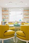 Runde Sitzecke mit gelben Polstersesseln & rundem Glastisch