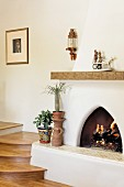 Fire in fireplace next to wooden stairs; Santa Fe; New Mexico; USA