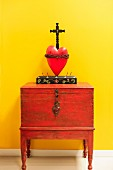 Crucifix over red heart and cabinet against yellow wall; Santa Fe; New Mexico; USA