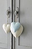 Drei Deko-Herzen hängen an Türgriff von Kommode