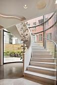 Weisser Treppenaufgang mit Wendeltreppe & Dekoobjekt aus Kugeln in Luxus-Hotel
